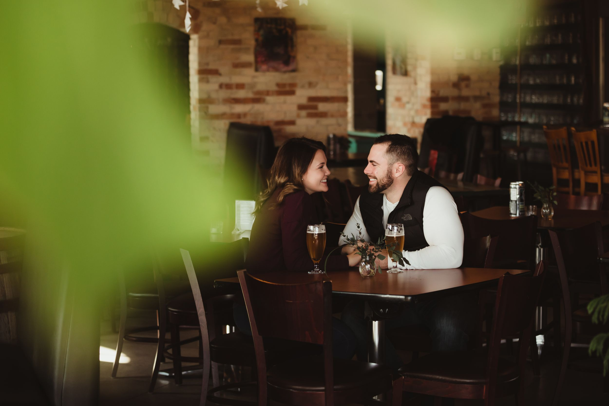 A man and woman sitting at a table in a brewery smiling at each other.