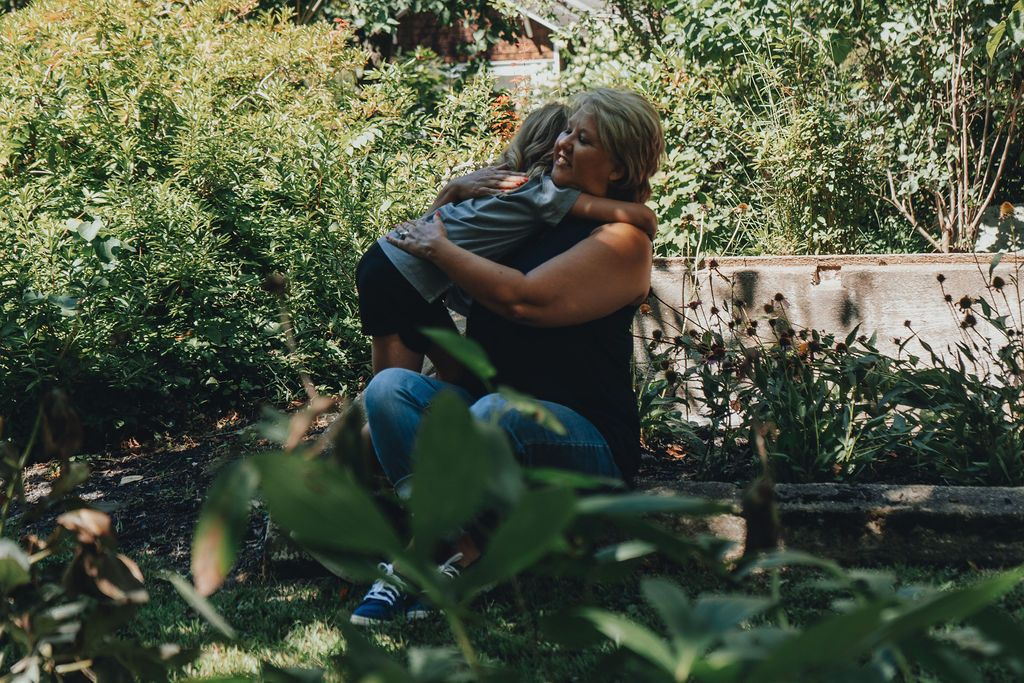 Granddaughter hugging grandmother at the park while grandmother sits in the garden area of Sayen Gardens, New Jersey