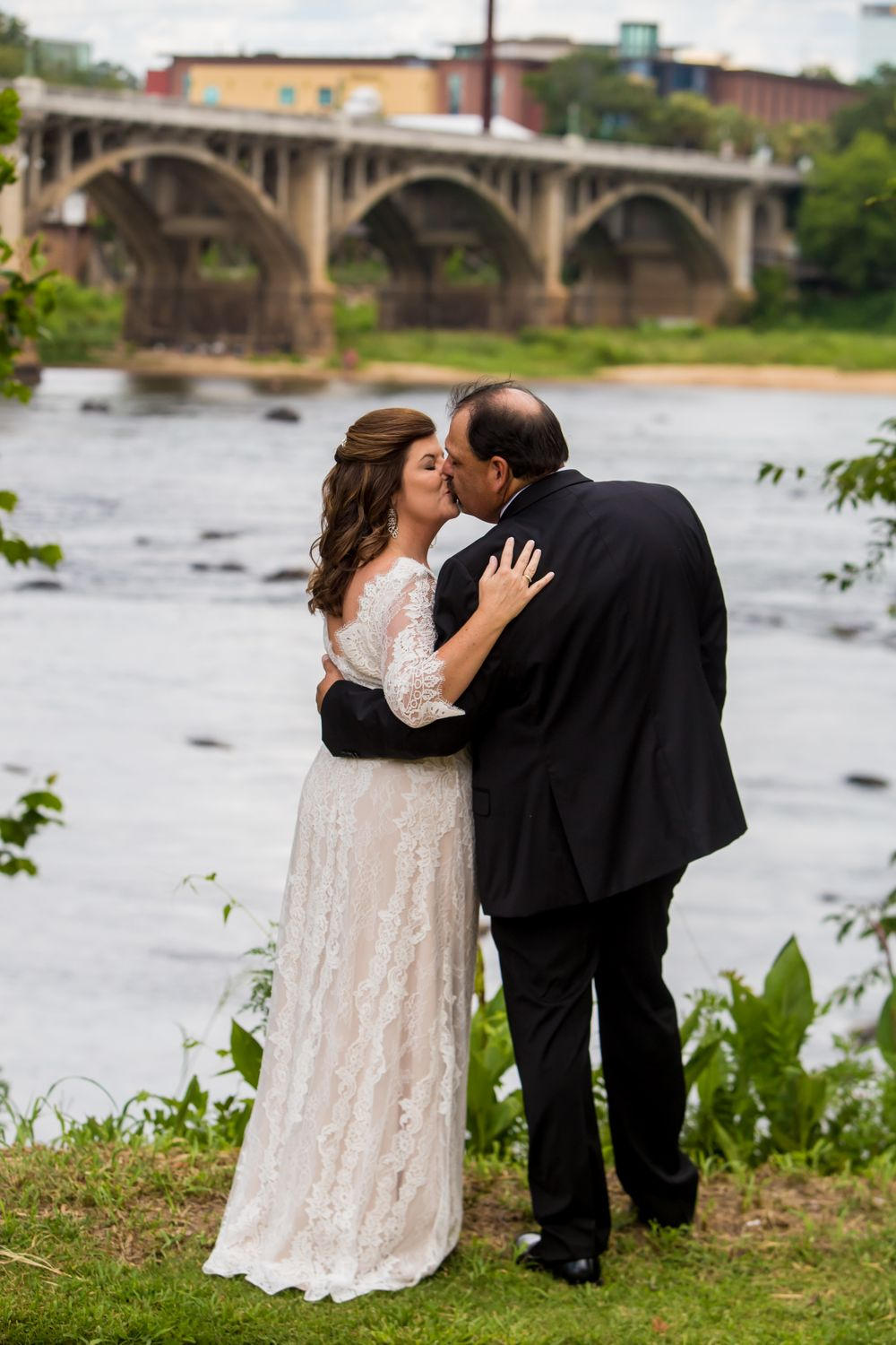 Bride & groom kiss w/ the Congaree River and Gervais St. Bridge behind them following their wedding at Stone River
