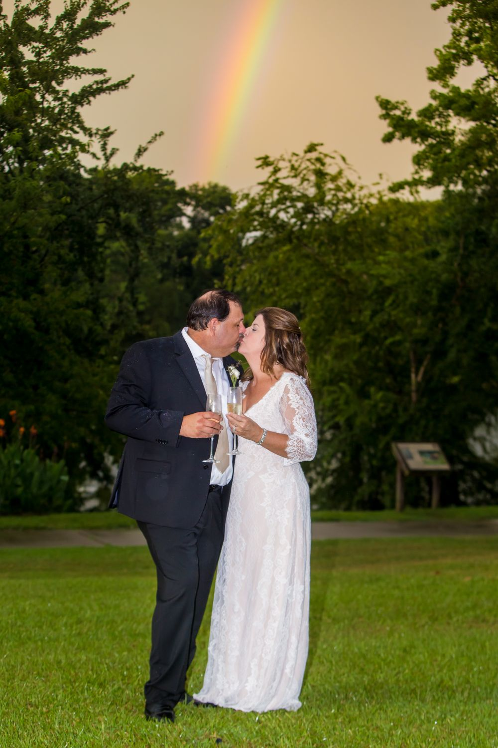 Bride Wendee and groom Bill kiss in front of a rainbow following their wedding at Stone River in West Columbia, SC