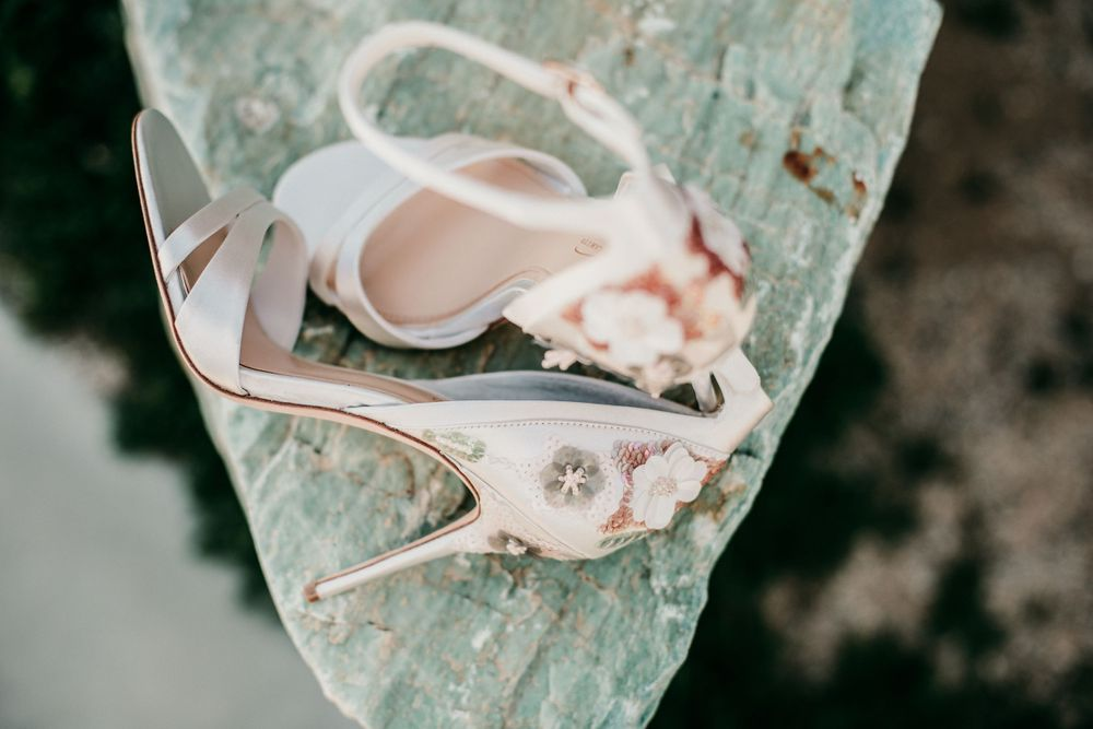 pink bridal shoes on green stone