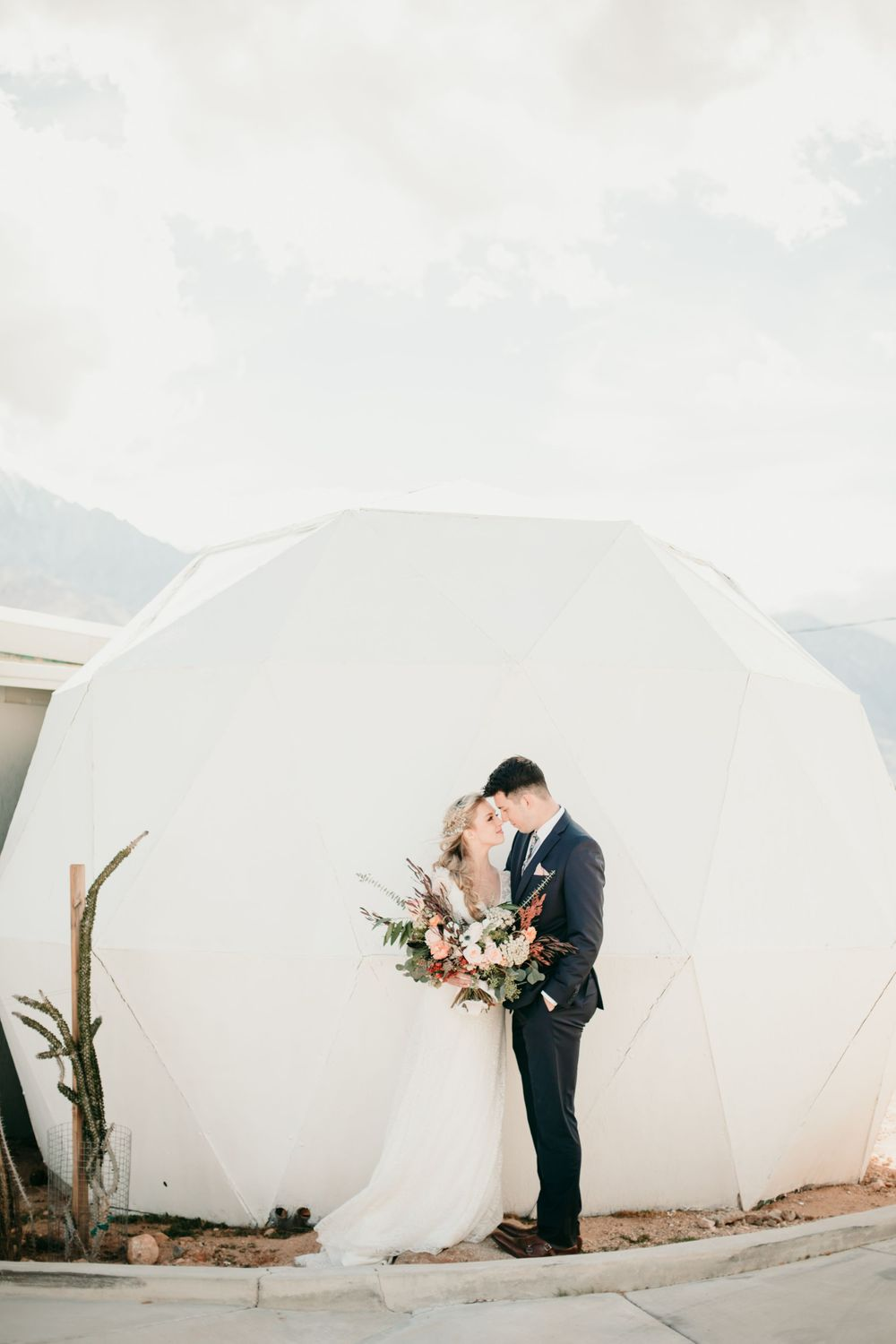 bride and groom standing by unique tent
