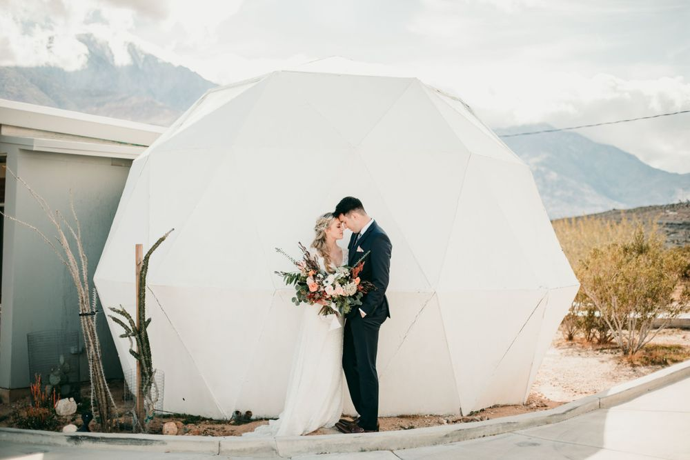 bride and groom standing by tent