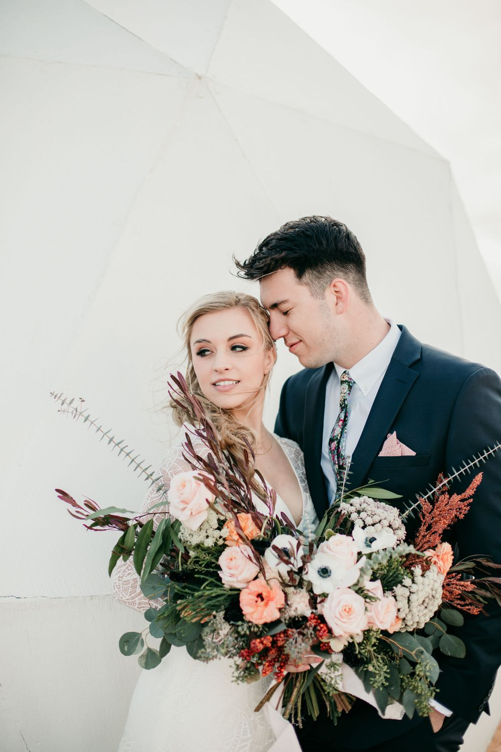 stylish bride and groom holding large bouquet