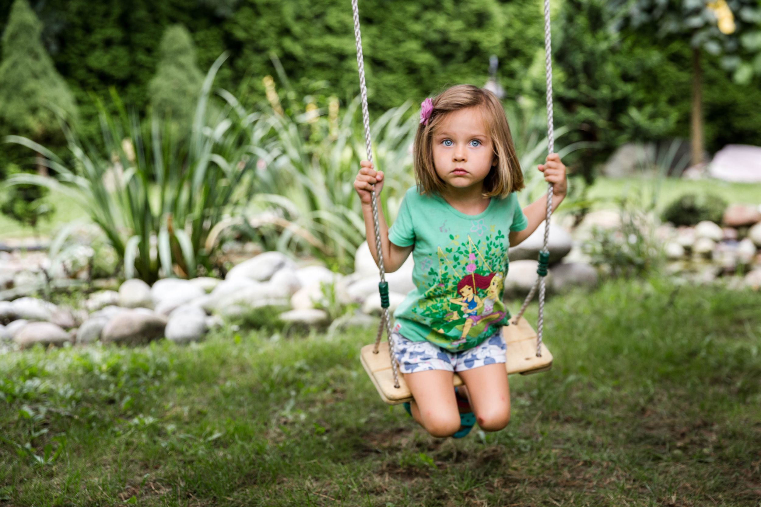 girl in green t-shirt sitting on swing