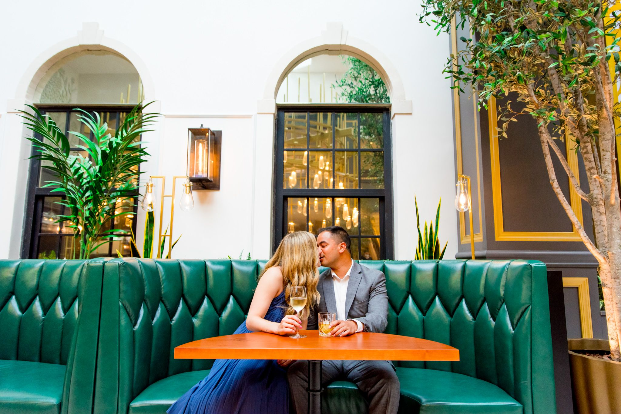 man in grey suit and woman in blue dress holding a glass of white wine kiss in green booth at Lytle Park Hotel