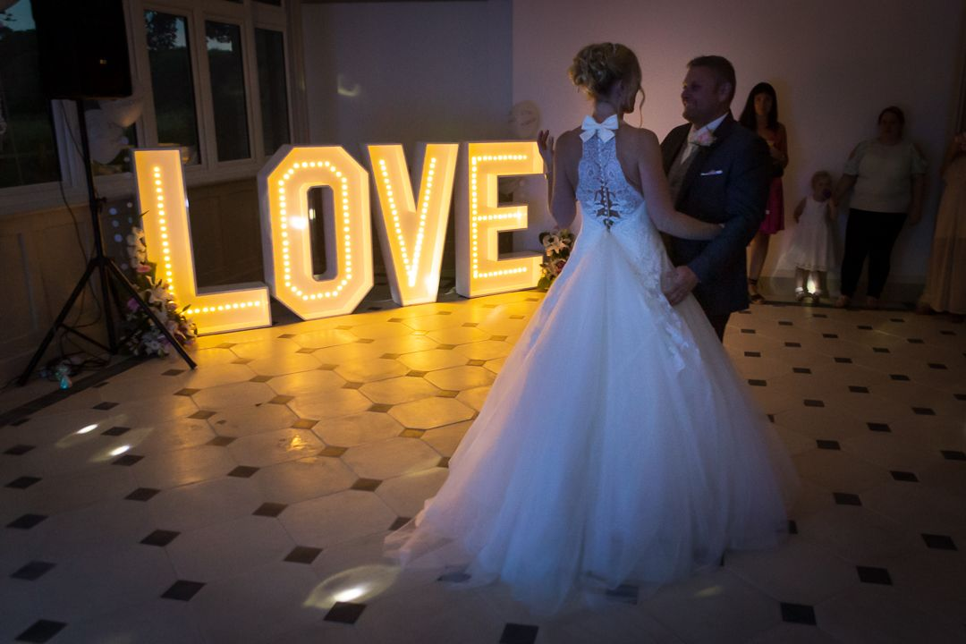 wedding couple first dance with illuminated love