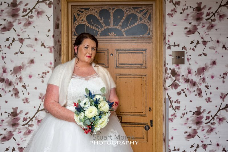 bride stands outside her hotel door painted to look like an ornate front door at oddfellows chester