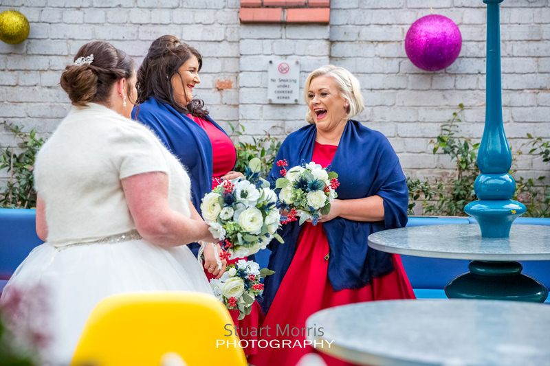 the bride and bridesmaids chilling laughing and joking before the ceremony in the garden room