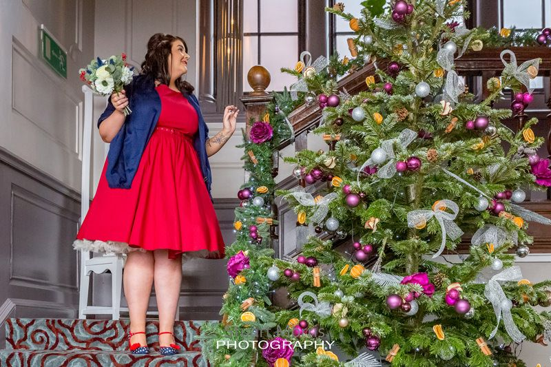 a bridesmaid walks down the stairs at oddfellows next to a giant christmas tree in the reception