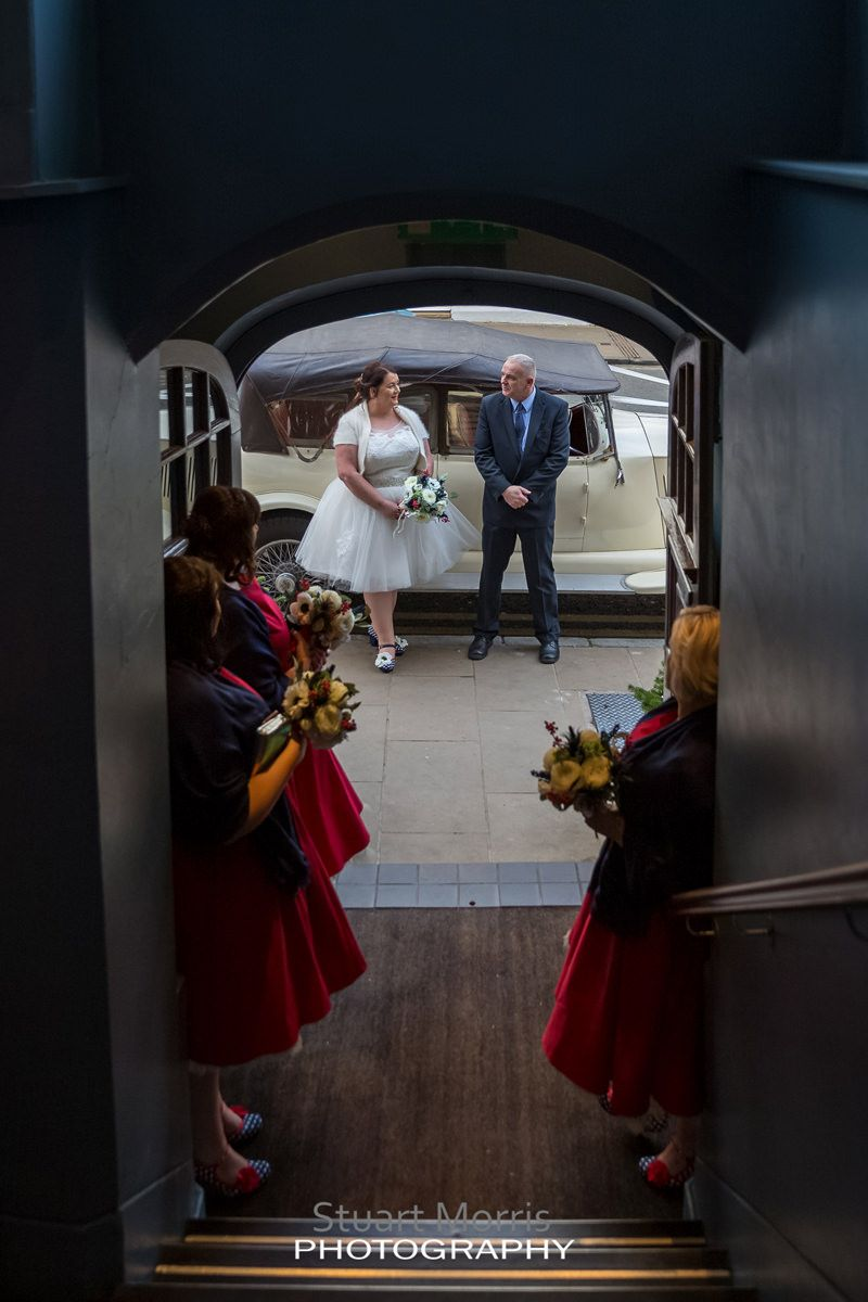 bride stands by the wedding car as the bridesmaids watch in the doorway at oddfellows