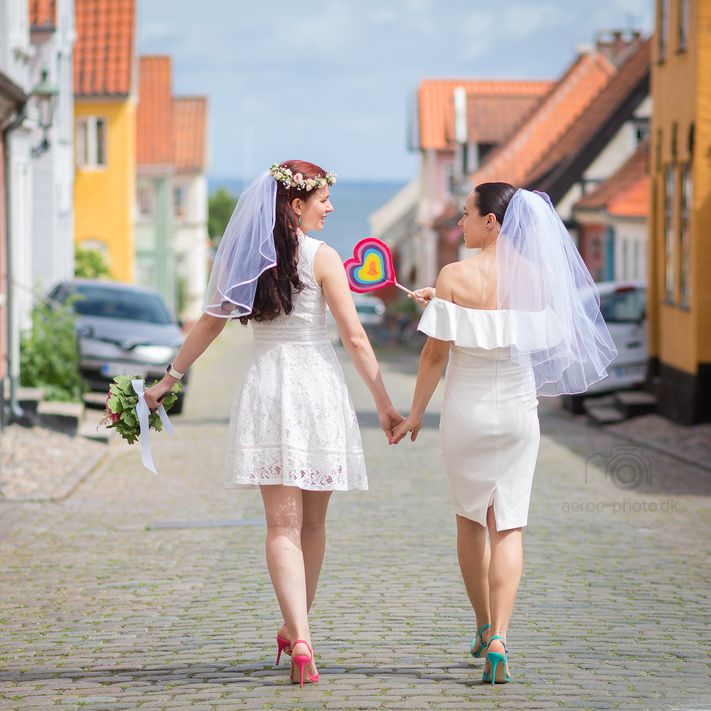 Two brides in white along the streets of Ærø.