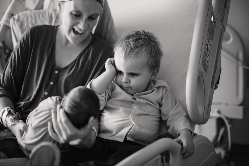 New mom shows little brother to toddler in black and white photo