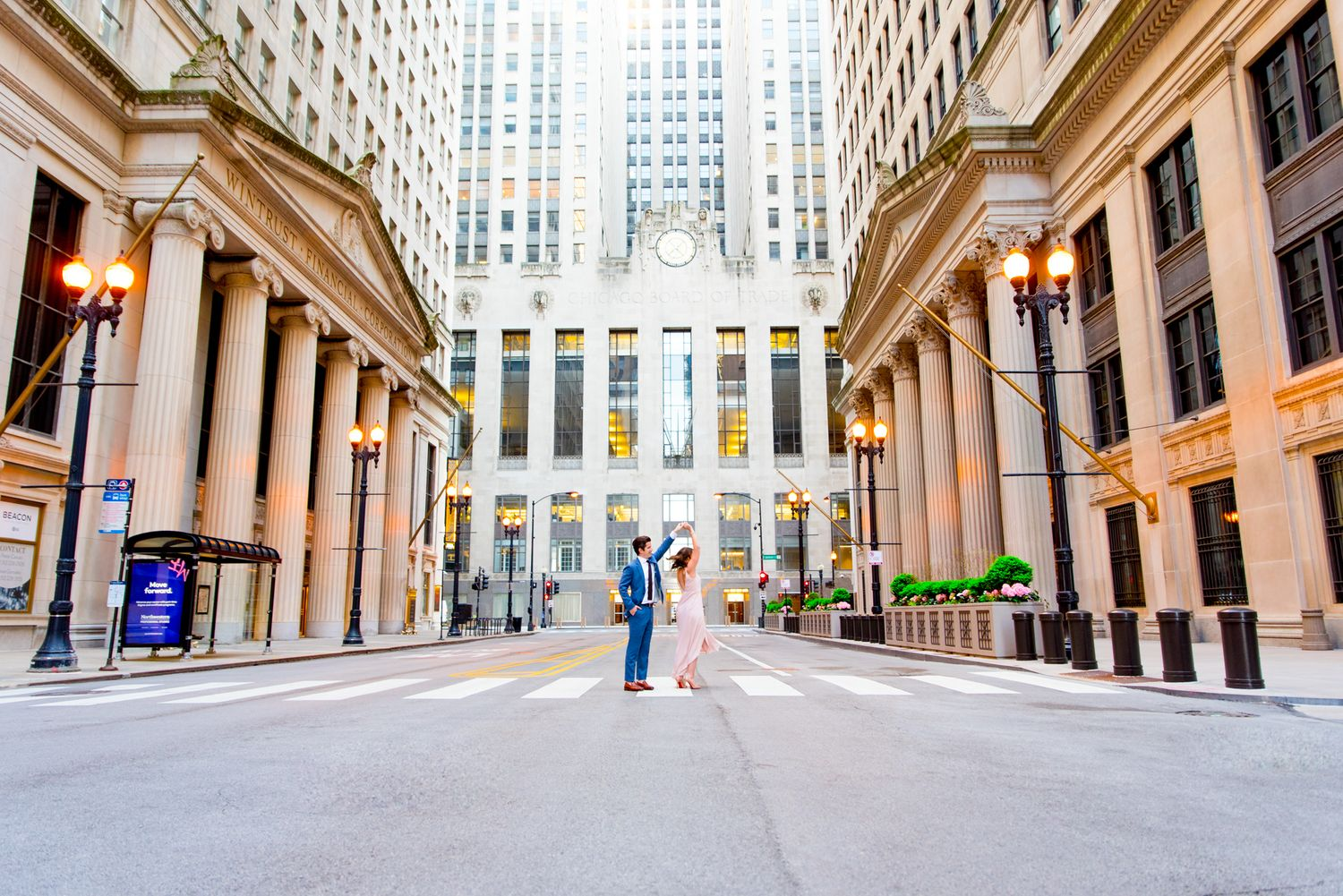 man in navy suit spins woman around in front of Chicago Board of Trade in empty street at sunset
