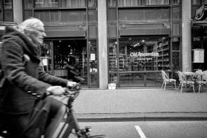 Black and White street photo of elderly lady on e bike outside the Amsterdam Old Cheese store in Amsterdam, NL.