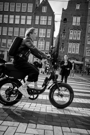 black and white street photograph of a woman riding an e bike across a crossing in Amsterdam.