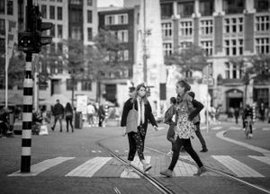 black and white street photograph of a likely collision between 2 women on a crossing in Amsterdam.