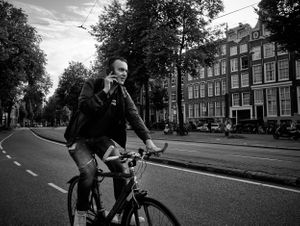 street photograph of man riding bicycle using phone in Amsterdam