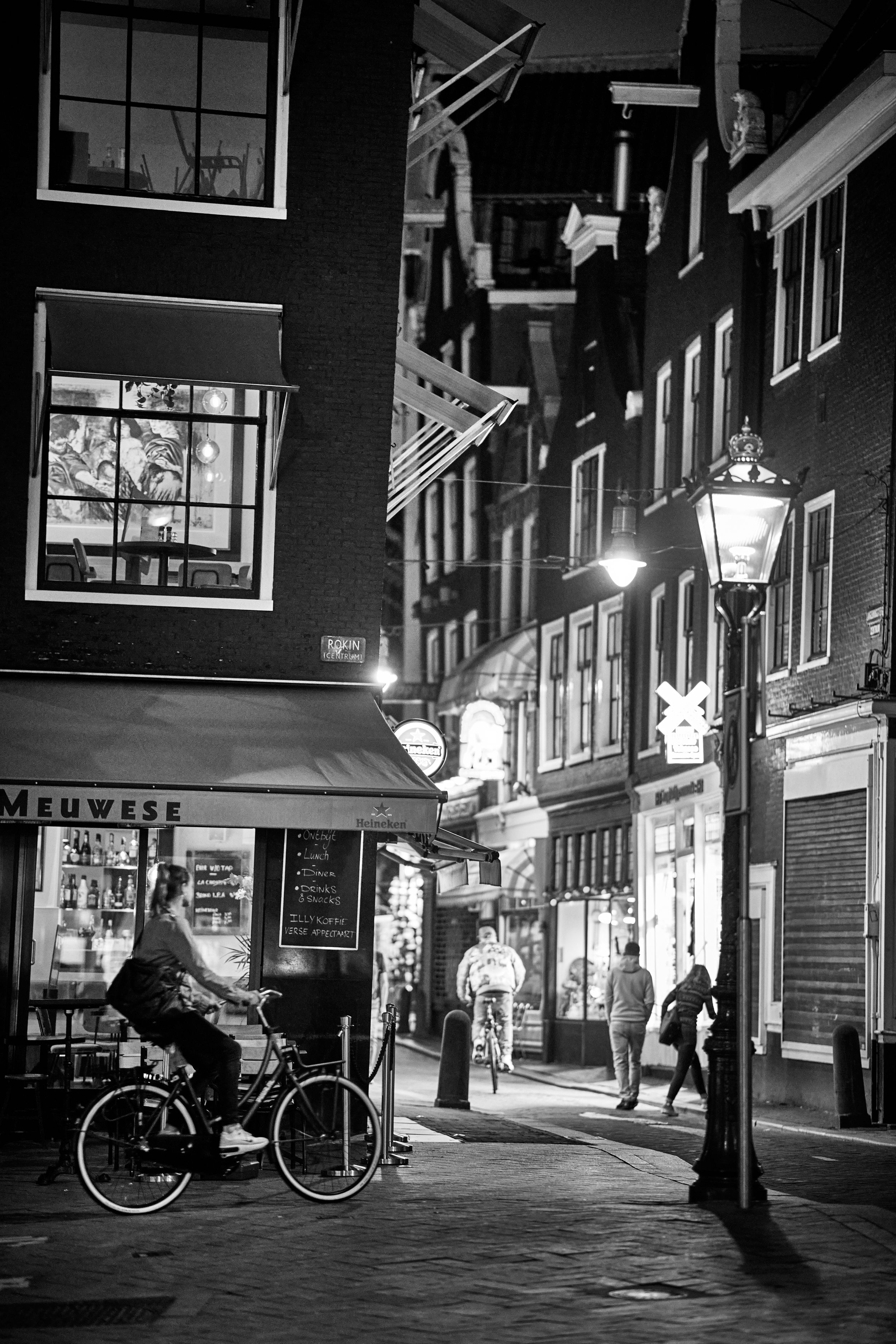 Photograph of lady riding bicycle at night in Amsterdam