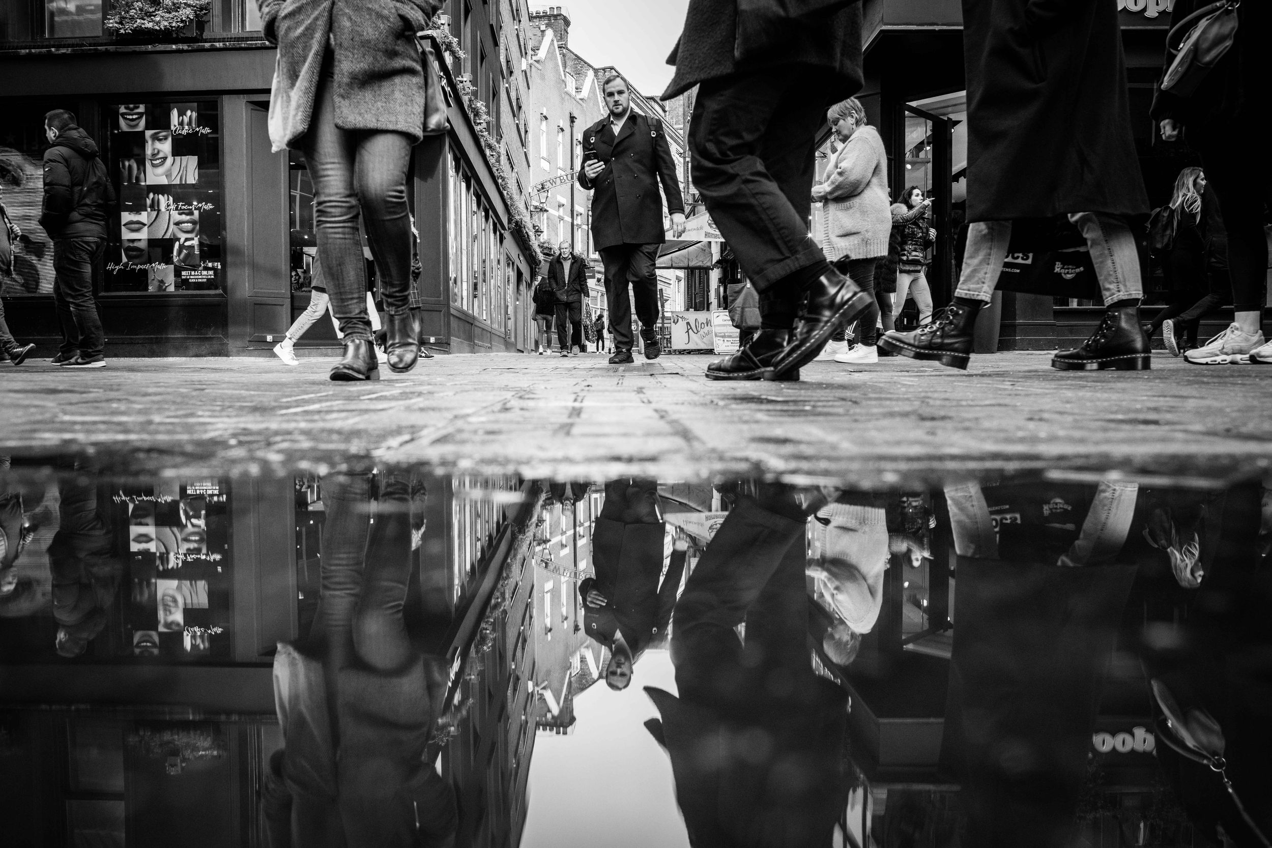 Black and white street photo of man's reflection in puddle on Carnaby Street, London.