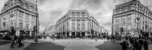Panoramic black and white street photograph of Oxford Circus, London.