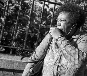Black and white street photo of a woman yawning.