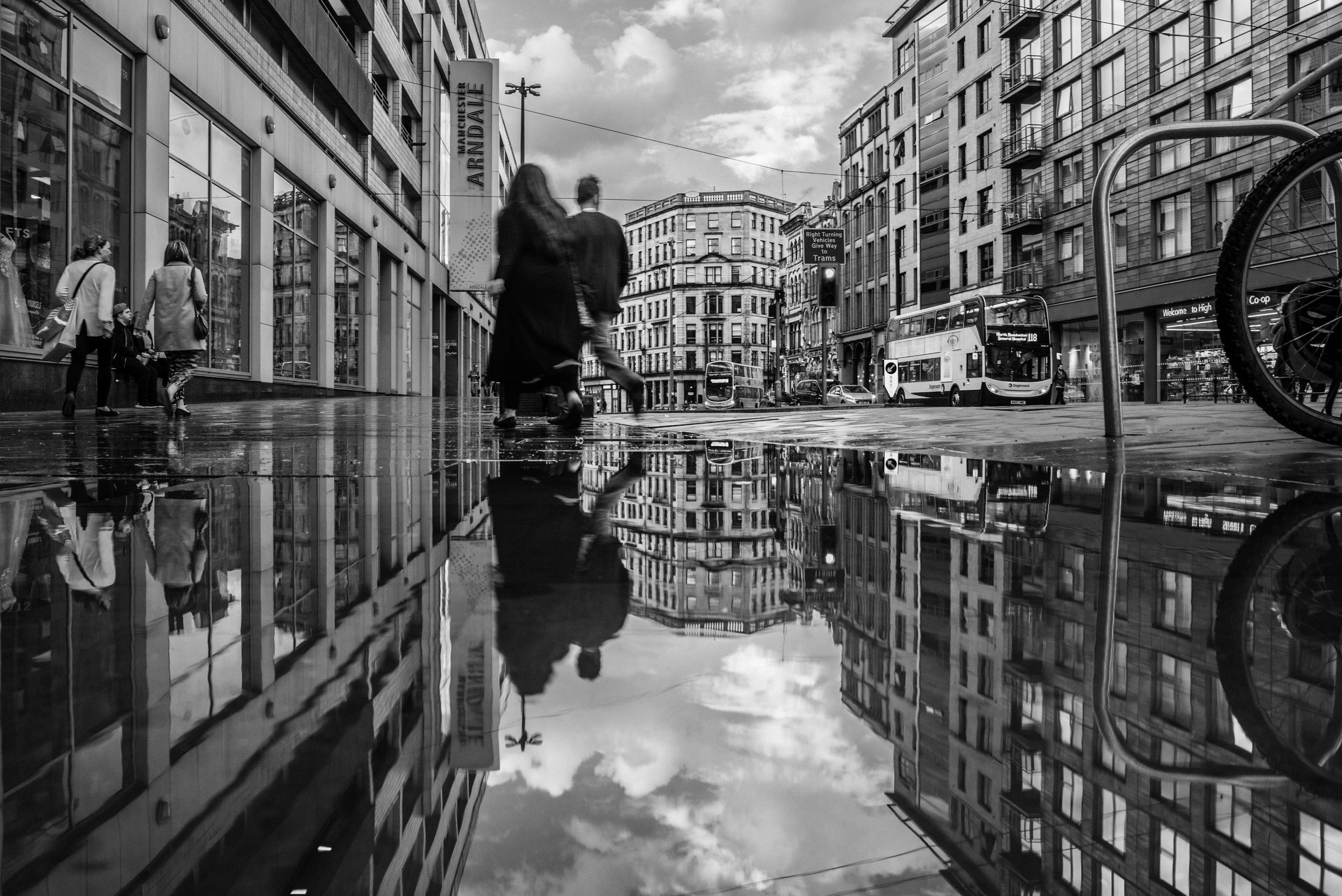 A shot of Sudehill in Manchester, symmetrical reflection in a puddle of a relaxed street scene in black and white.