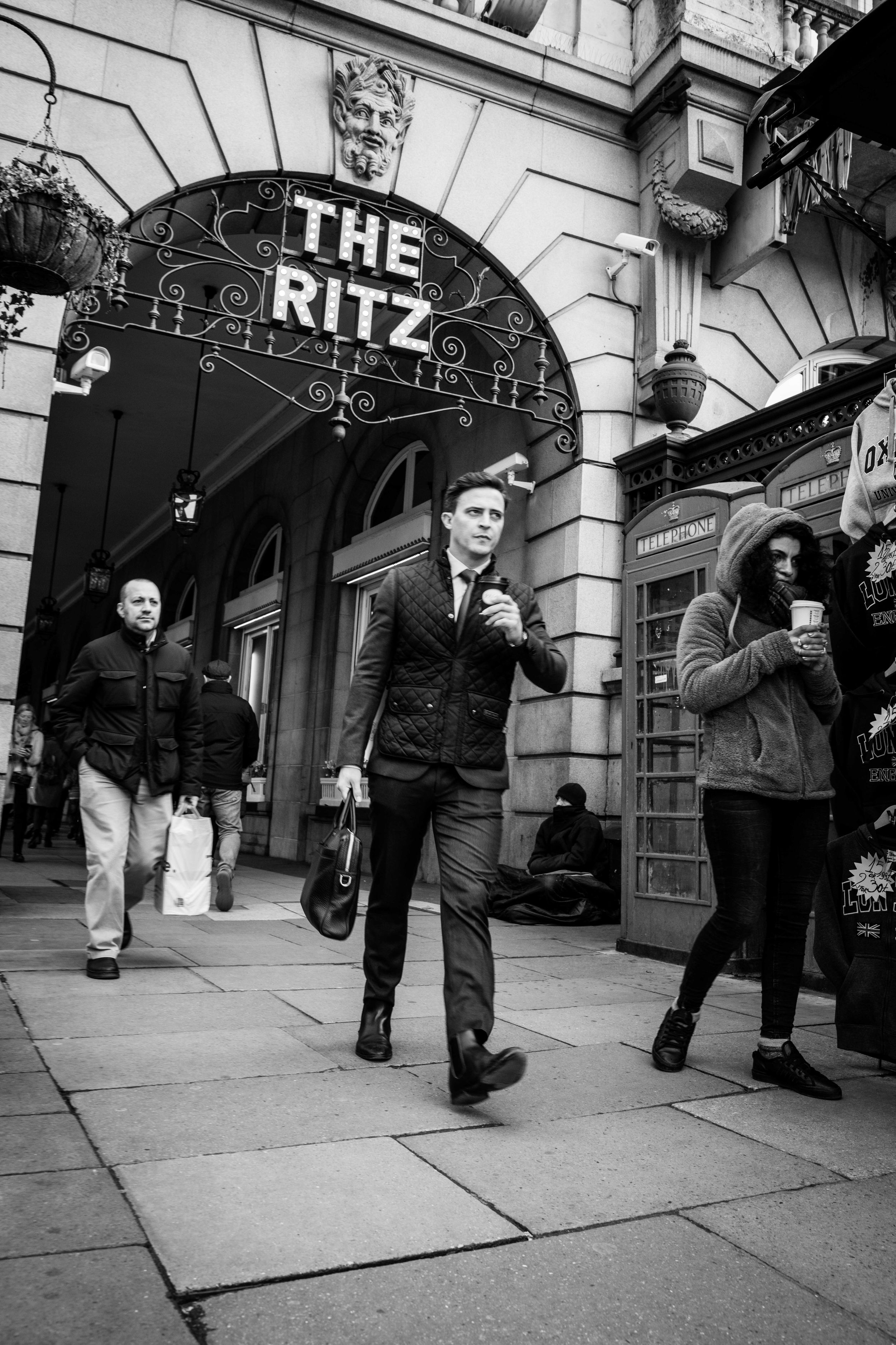 Black and white street photograph of commuters passing homeless man outside the Ritz Hotel, London.