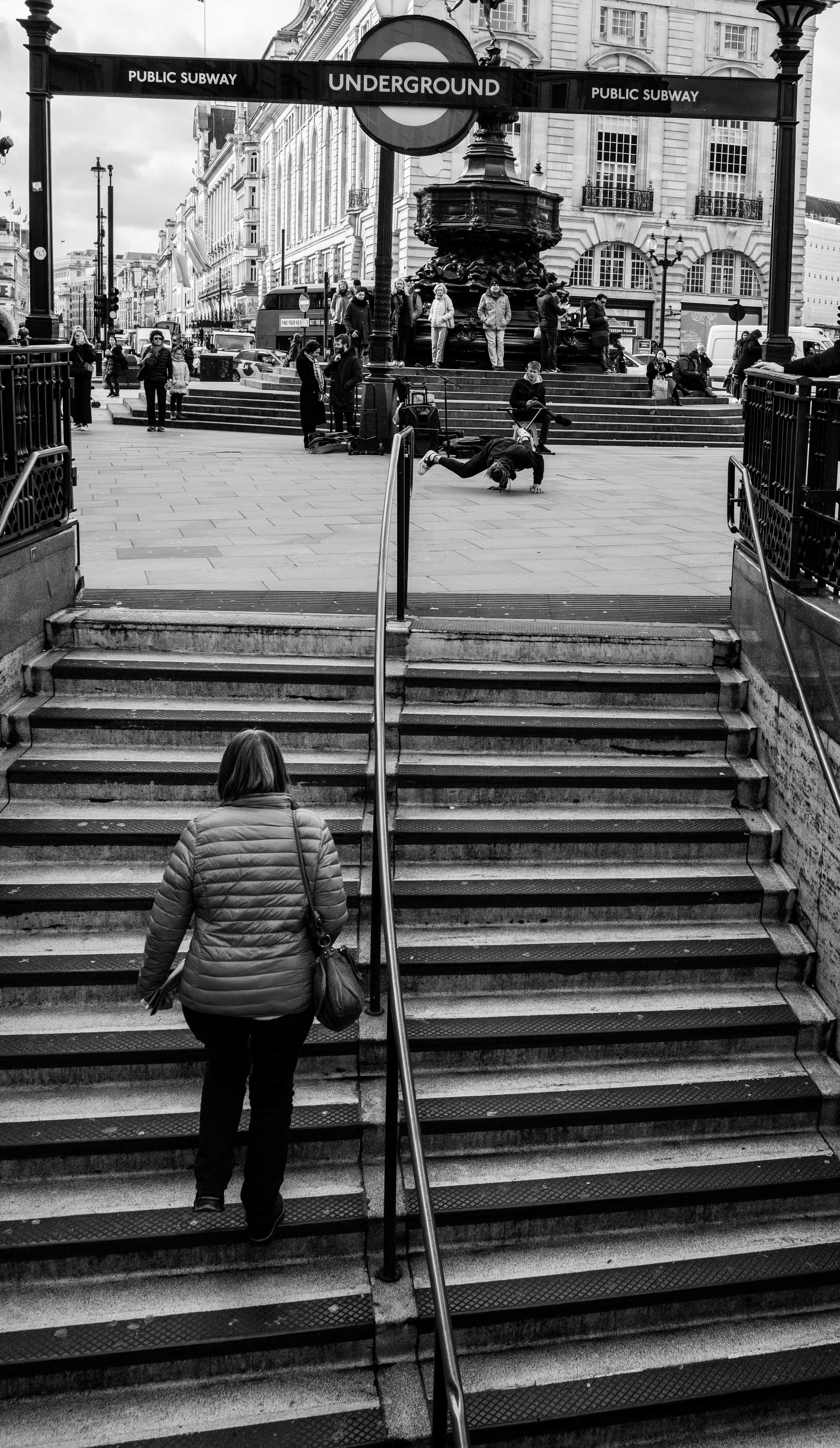 Lady walking up tube station stairs while man breakdances in black and white street photo.