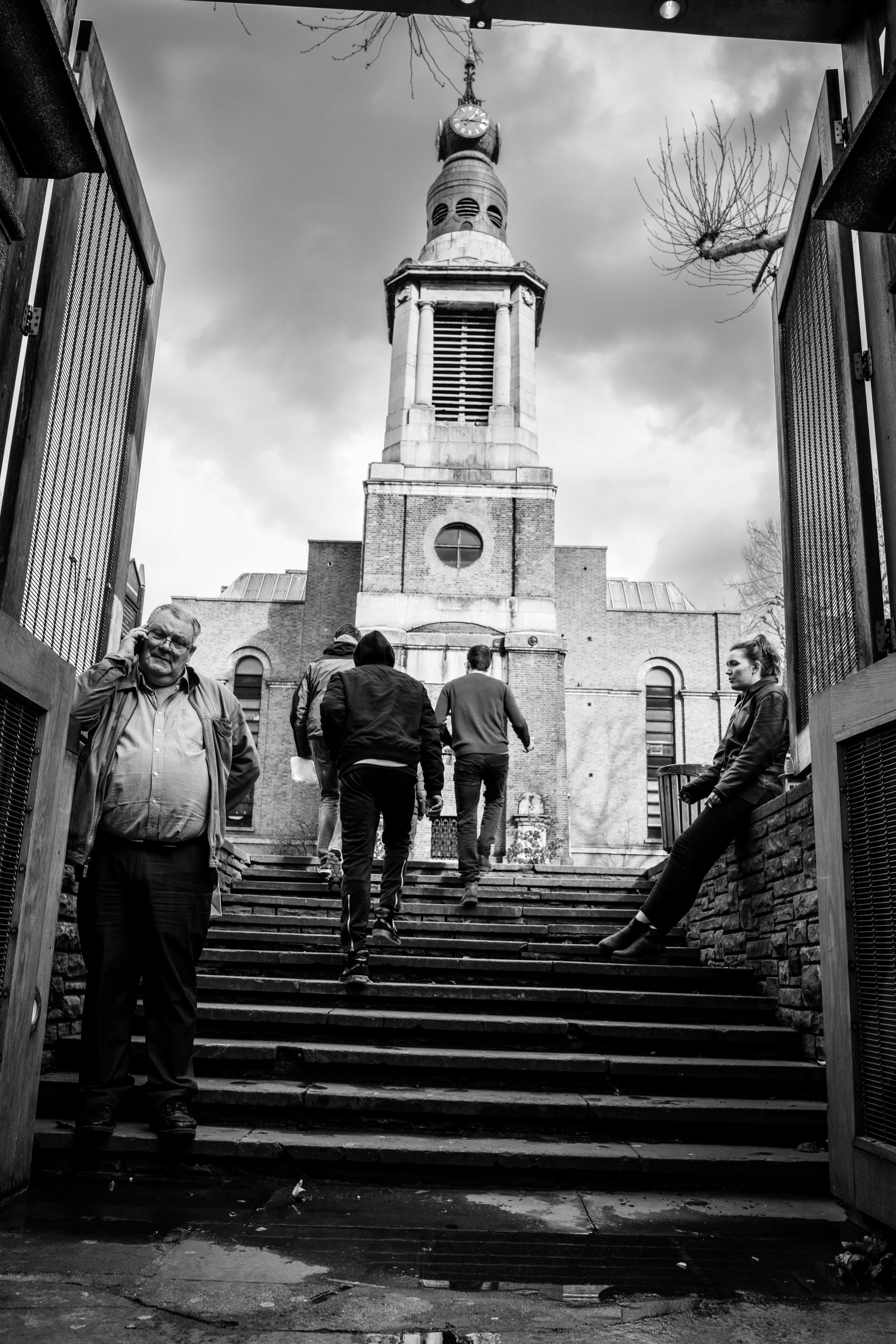 Black and white street photo of people living their lives on the stairs of an abandoned church in Soho, London.
