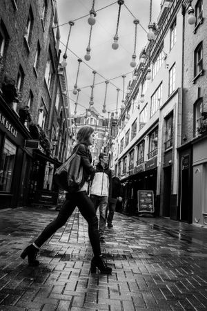 Black and white street photo of woman walking down Carnaby St, London.