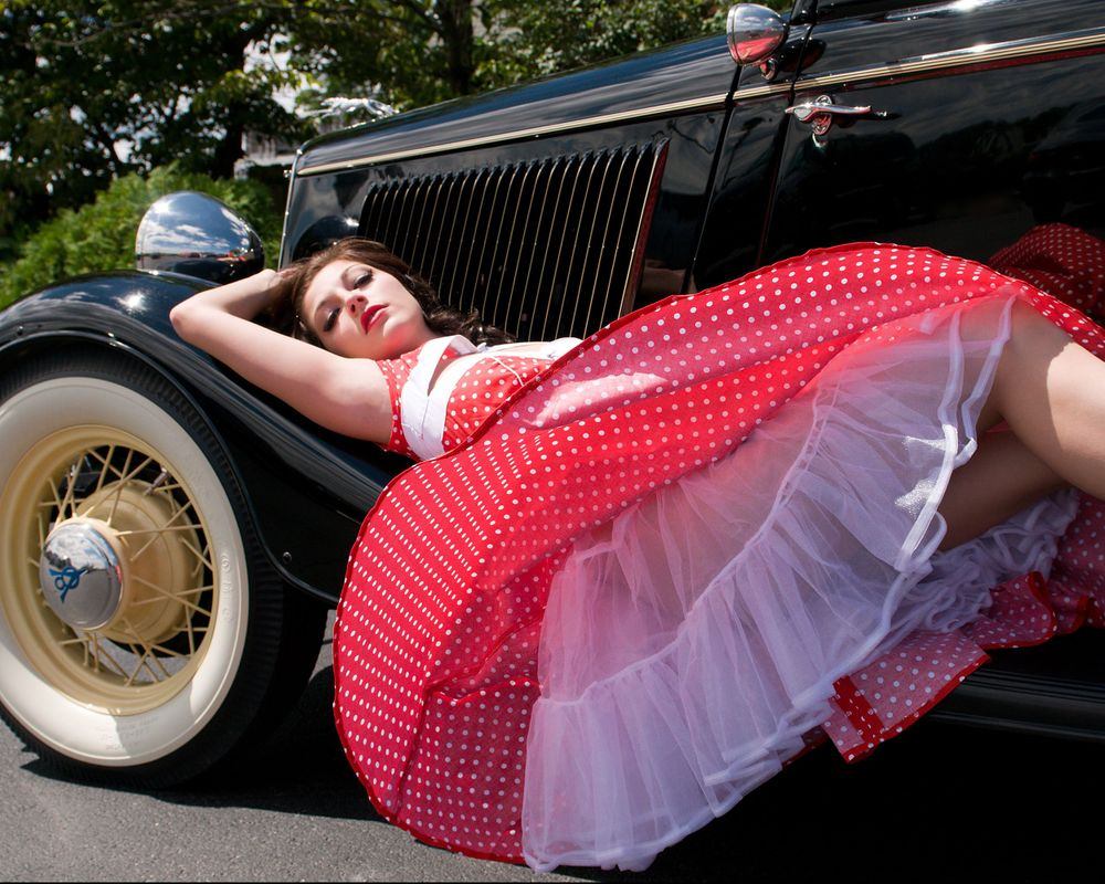 Beautiful young lady on fender of classic car