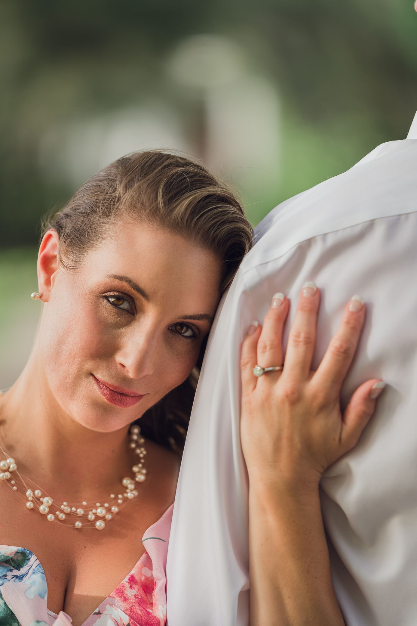 Future bride leaning of fiance and showing her ring for her engagement photoshoot at Caledonia Gold & Fish Club