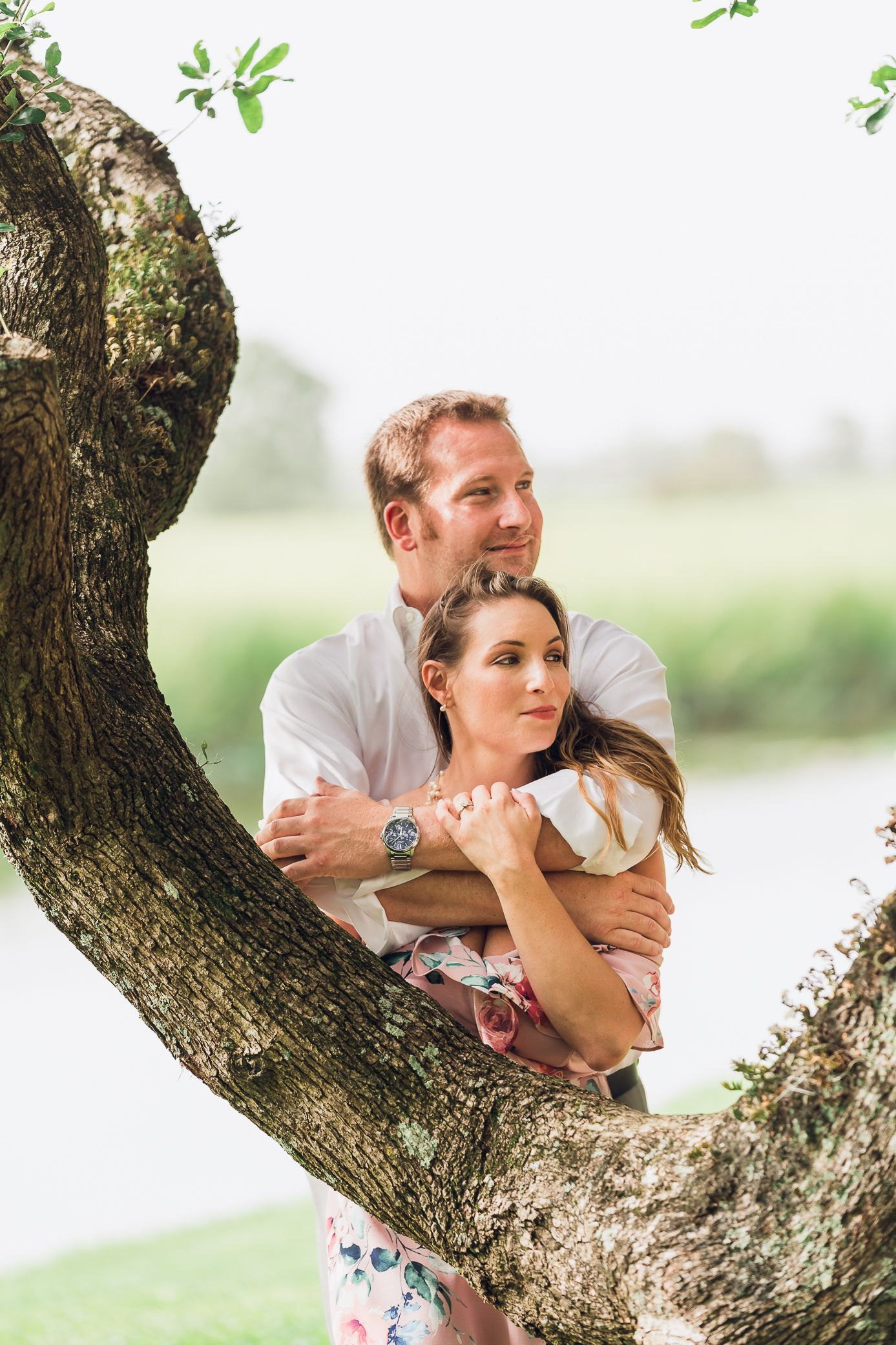 Future bride & groom Standing in front of a tree for their engagement photoshoot at Caledonia Gold & Fish Club