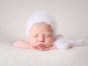 newborn baby girl with lilac bonnet
