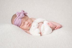 newborn baby girl in side pose with white bunny