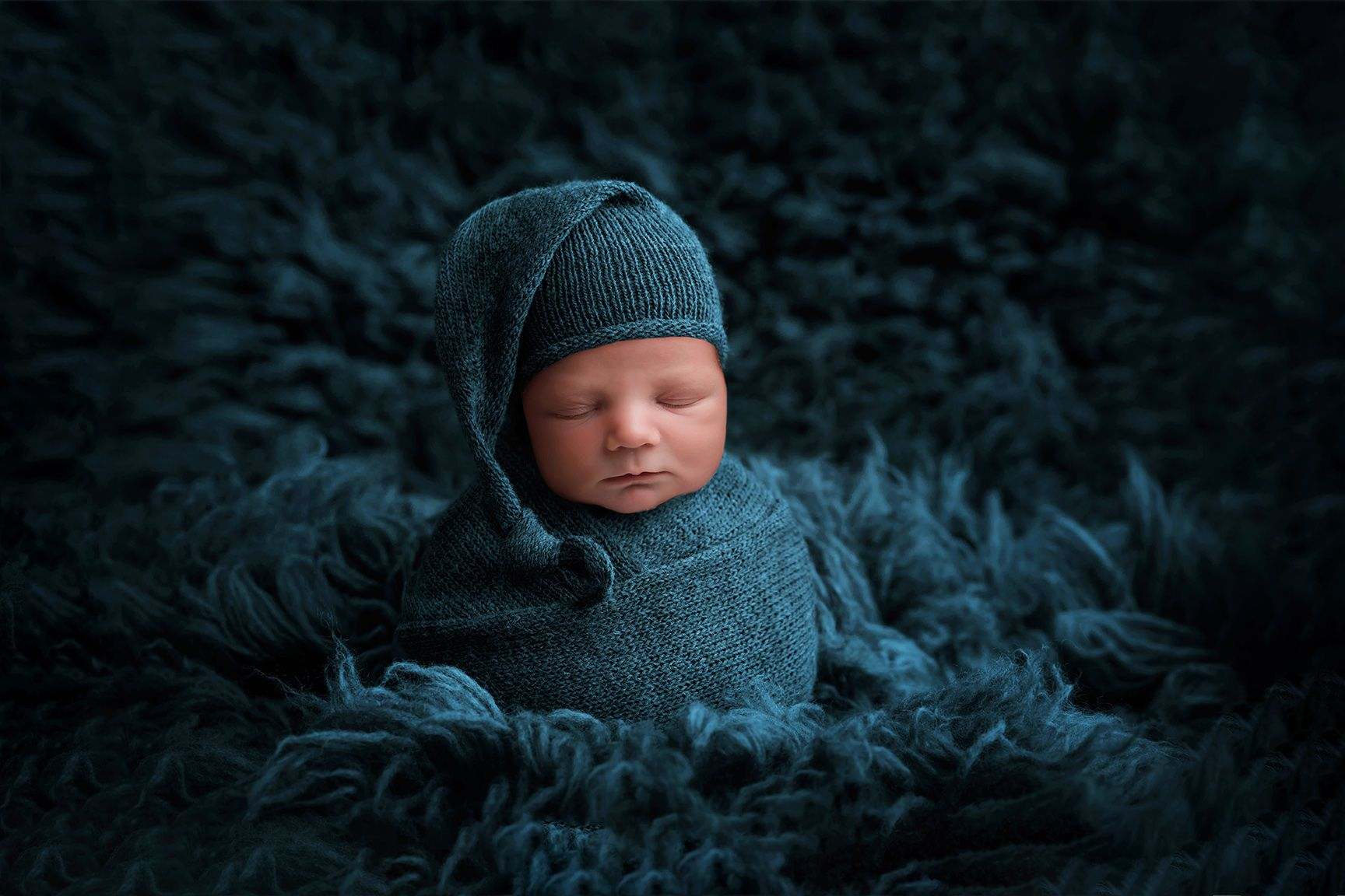 newborn baby wrapped and posed on blue rug
