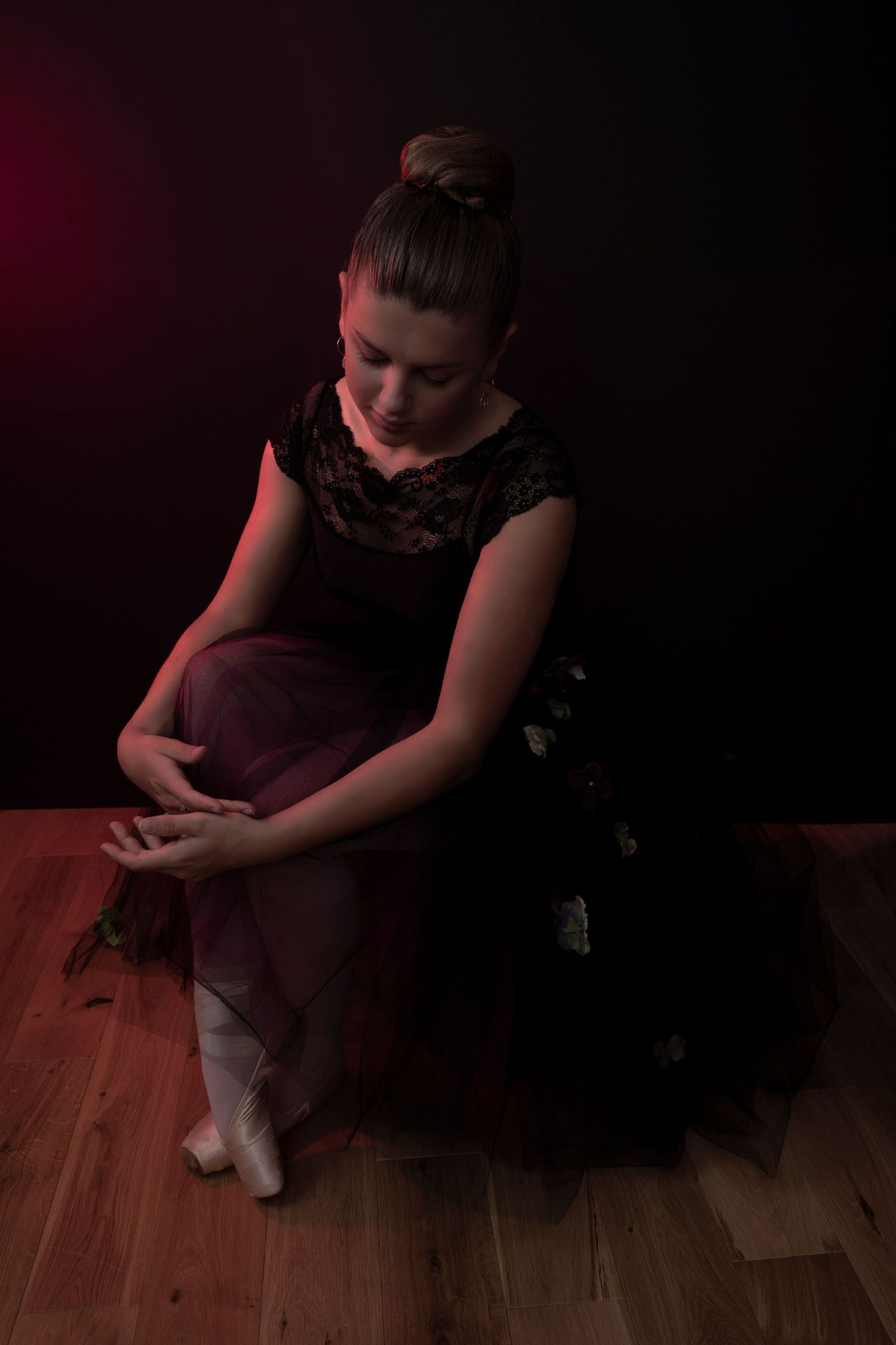 A ballerina sits on the floor wearing pointe shoes and a romantic tutu.