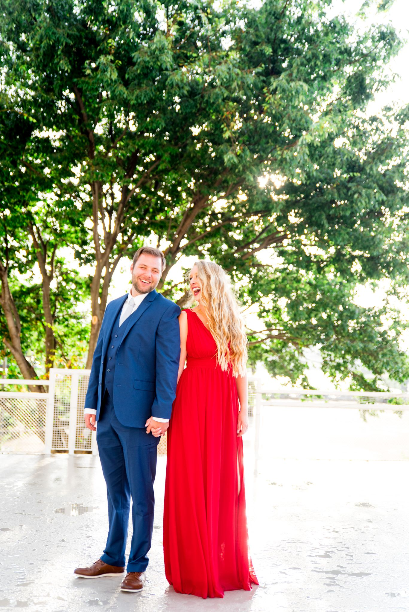 blonde woman in red dress and man in navy suit look at each other laughing in front of big tree