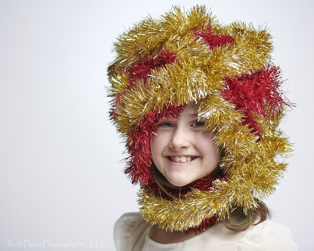 portrait of girl wearing headdress made of red and gold garland from the Christmas tree