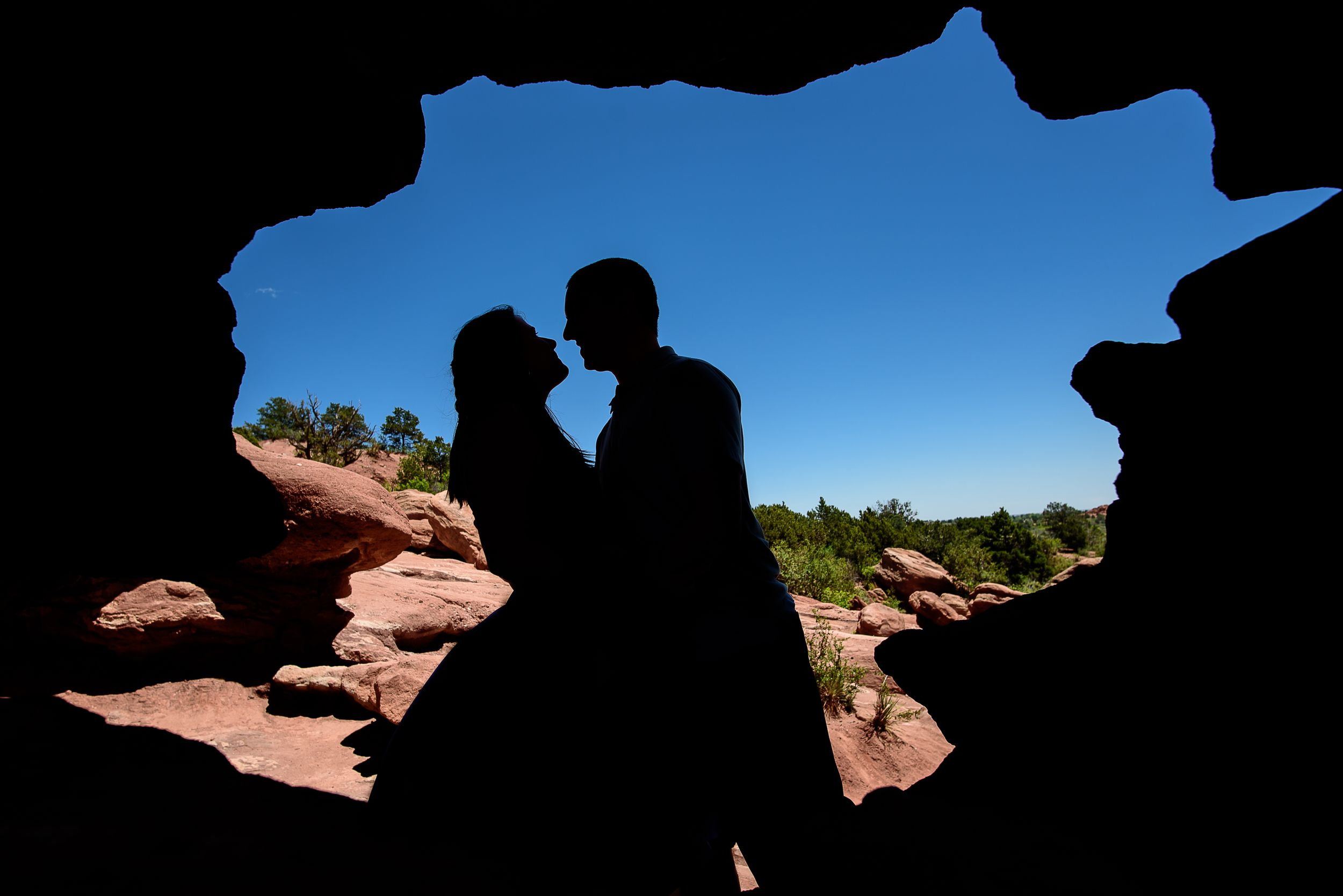 Unique raw edge silhouette of a couple in Garden of the Gods hiking in the mountains | adventurous wedding photographer