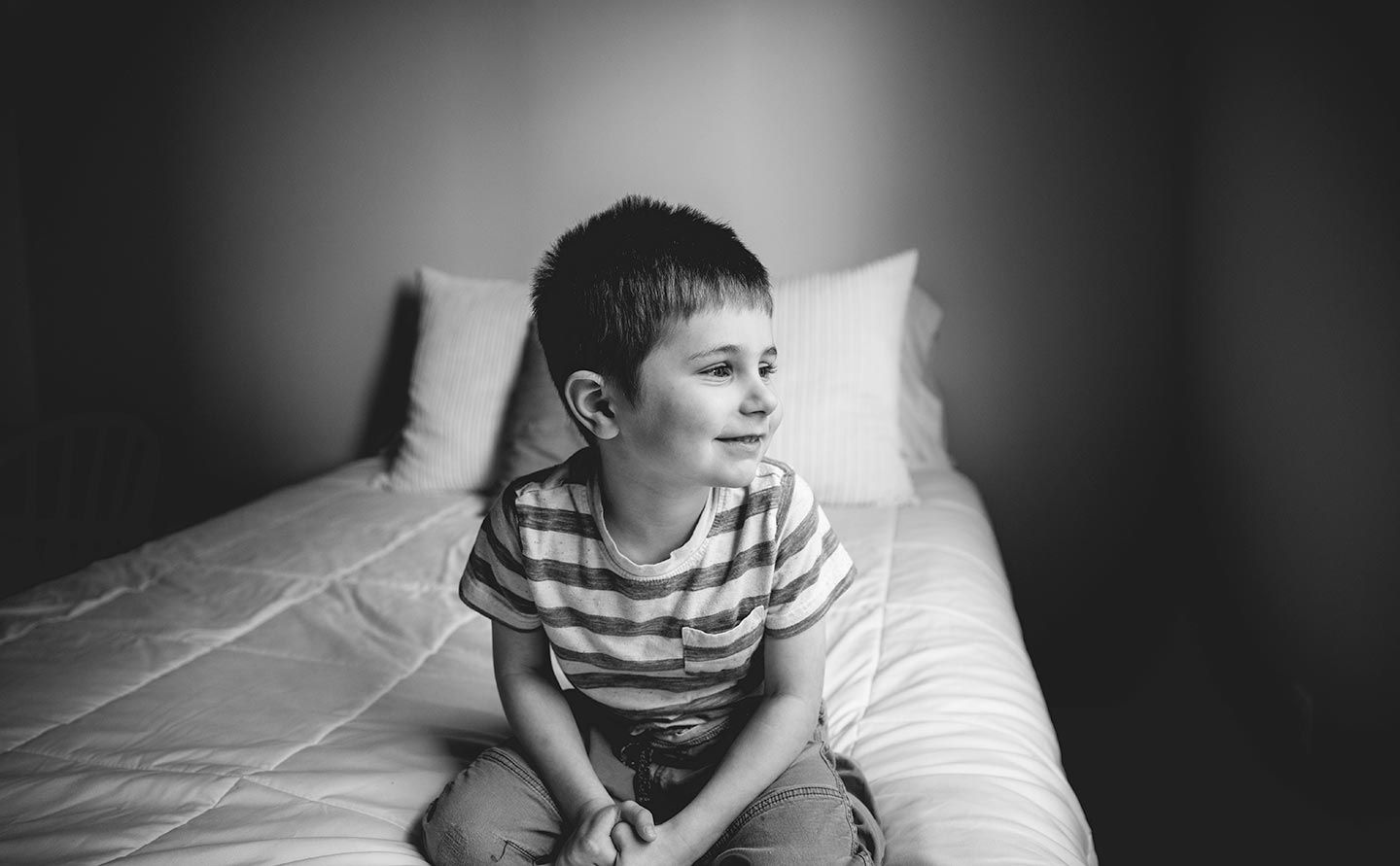 little boy smiling and looking out window