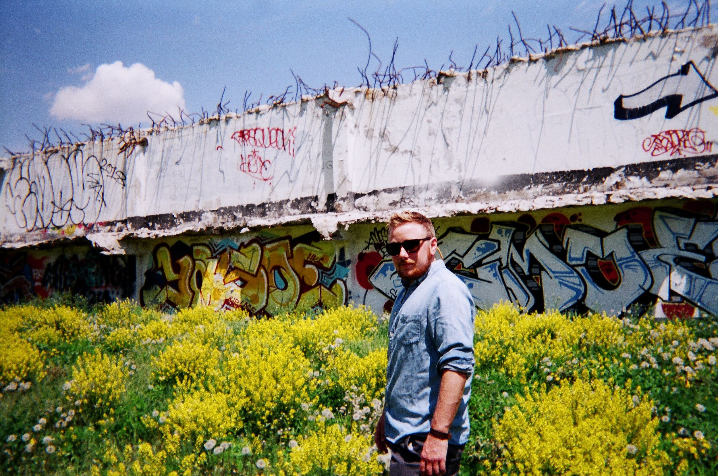 man wearing blue denim shirt in yellow field of flowers with graffiti wall nearby