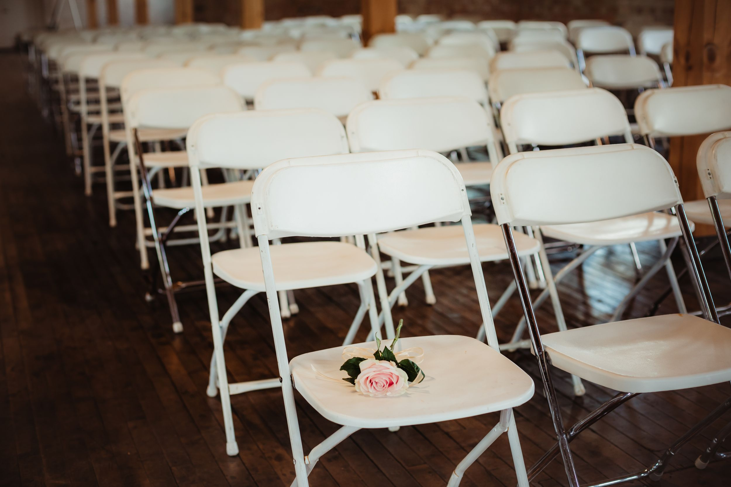 Single rose on an empty chair to represent the bride's late father.
