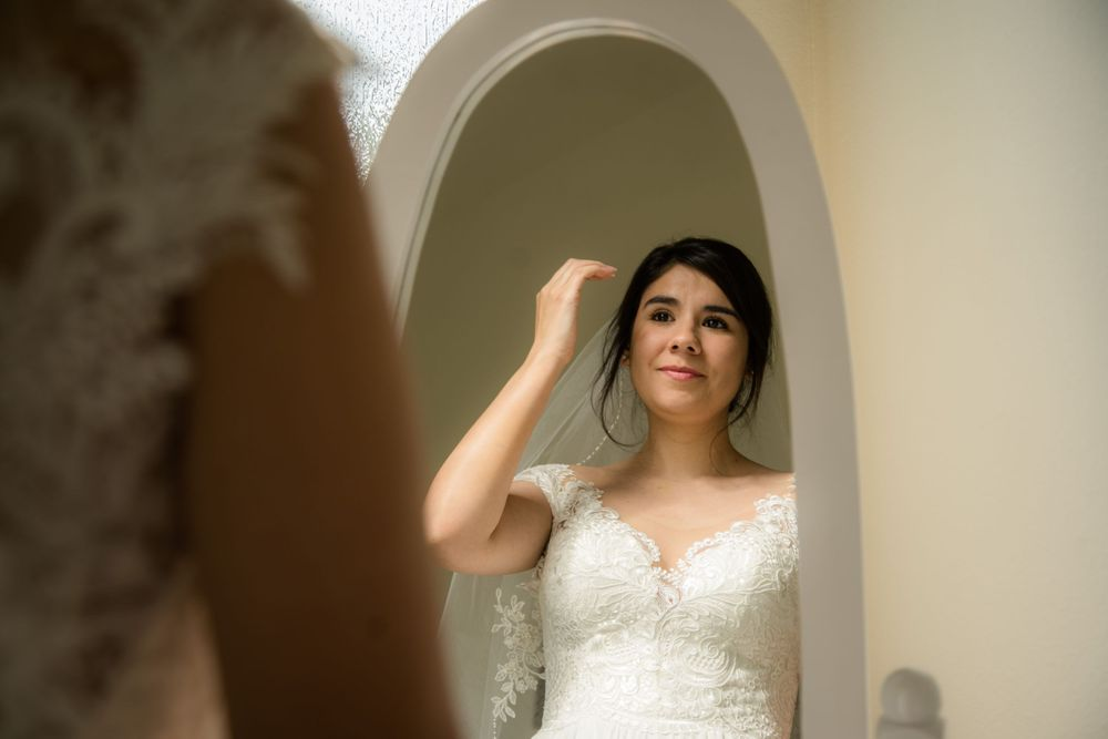 bride portrait in front of mirror while waiting to walk down the aisle
