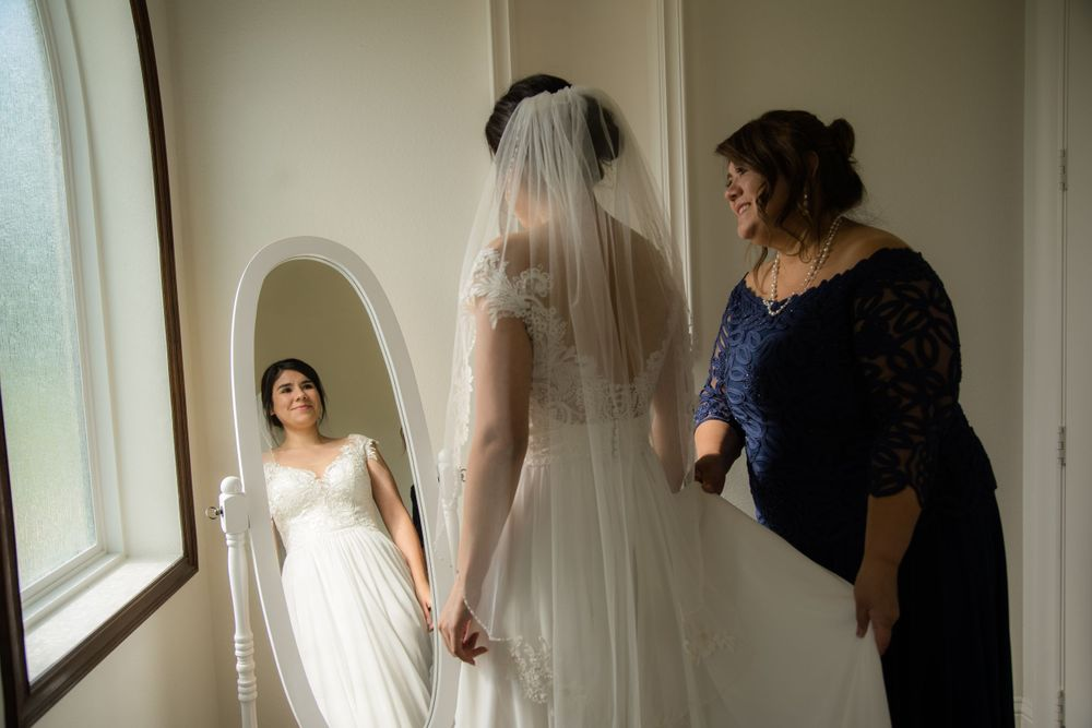bride and mom in front of mirror before the wedding ceremony