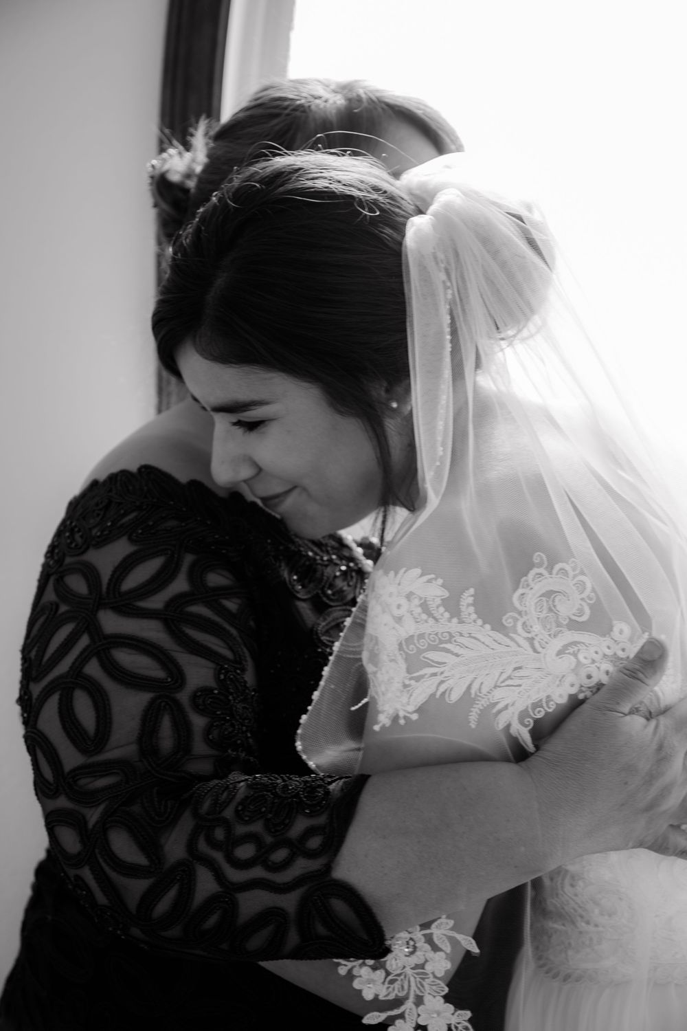 bride and mother of the bride hugging before the wedding ceremony