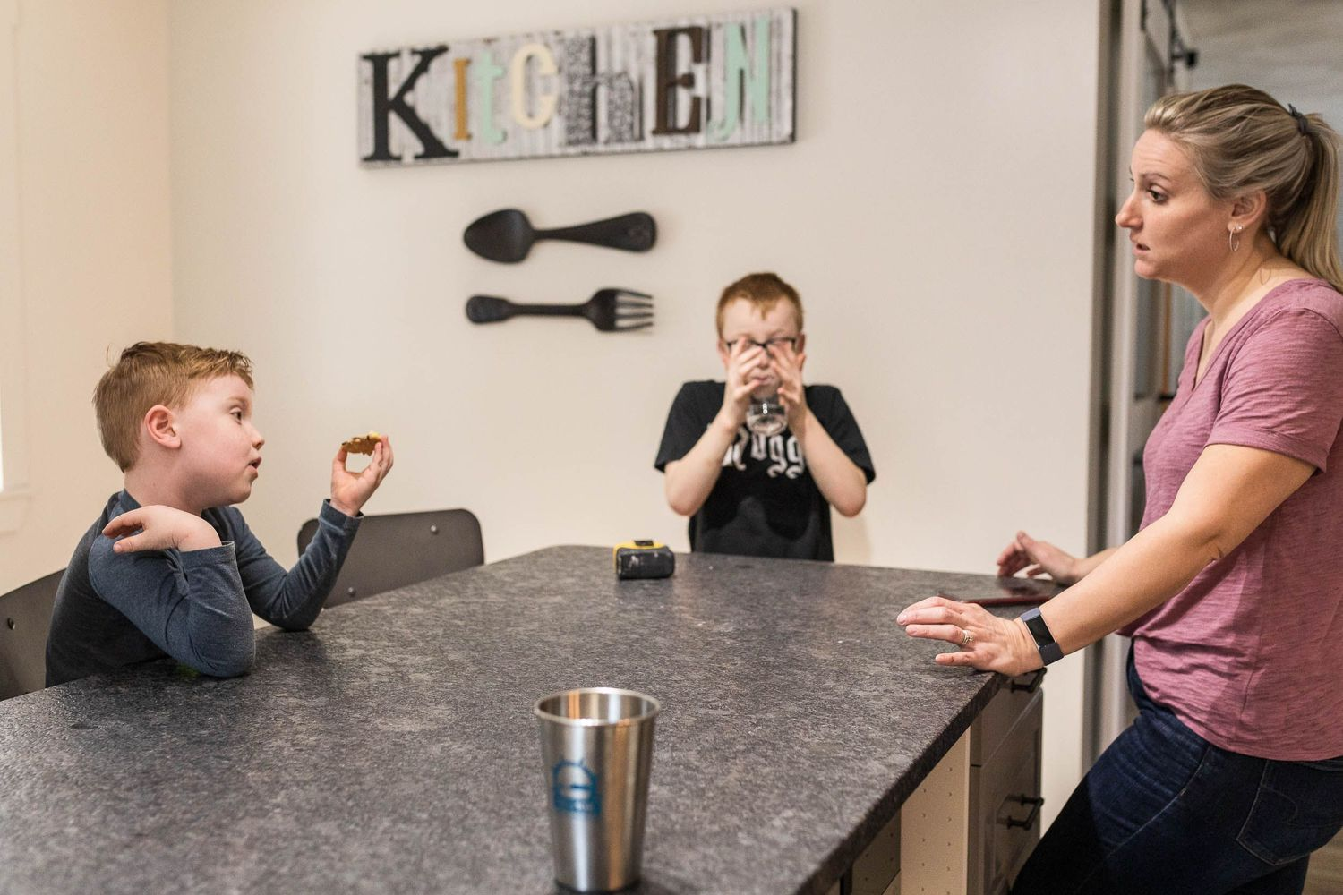 Mom talking to her two sons in the kitchen while they eat and drink in home session in Alton New Hampshire