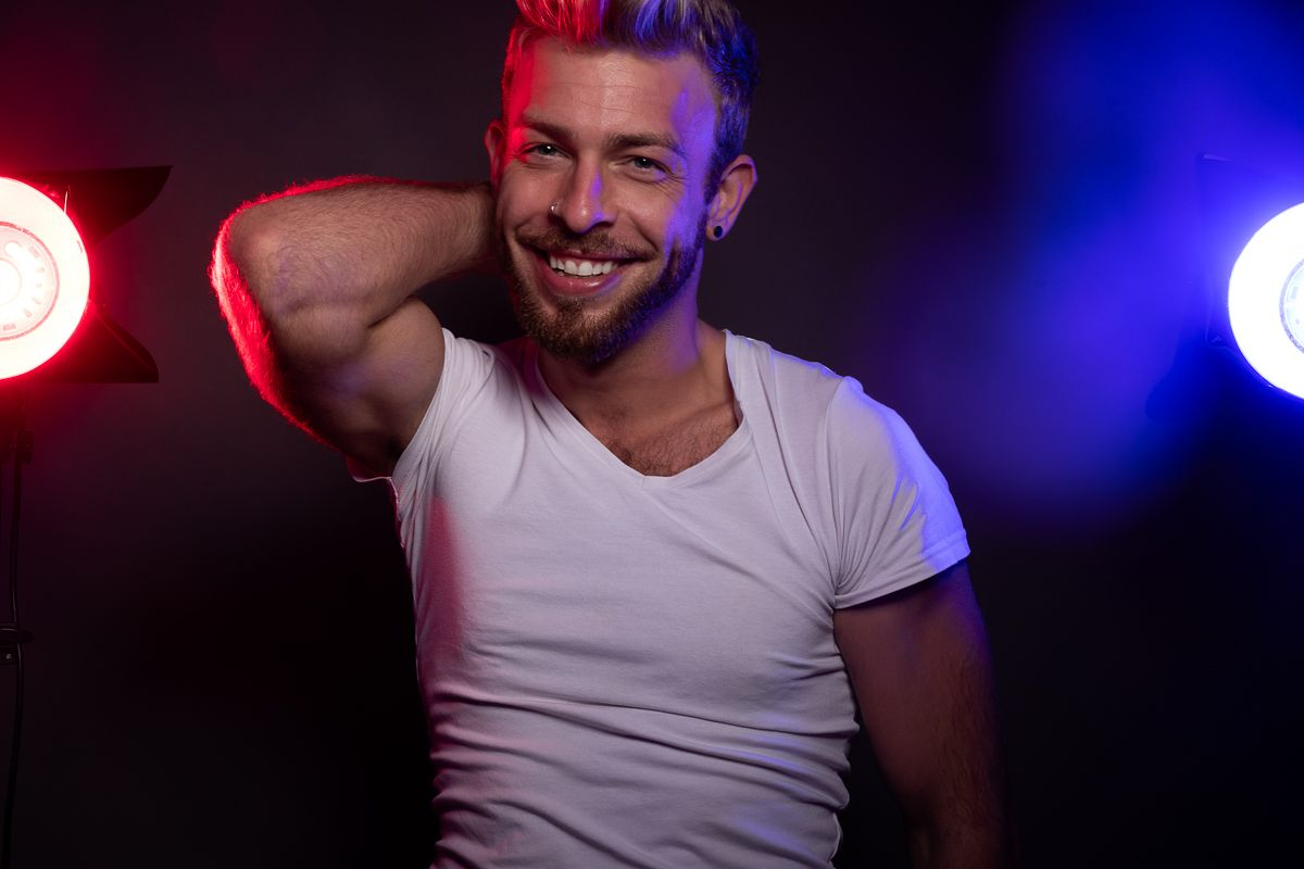 Adult model Gabriel Phoenix smiling with one hand behind his neck with colored lights on both sides