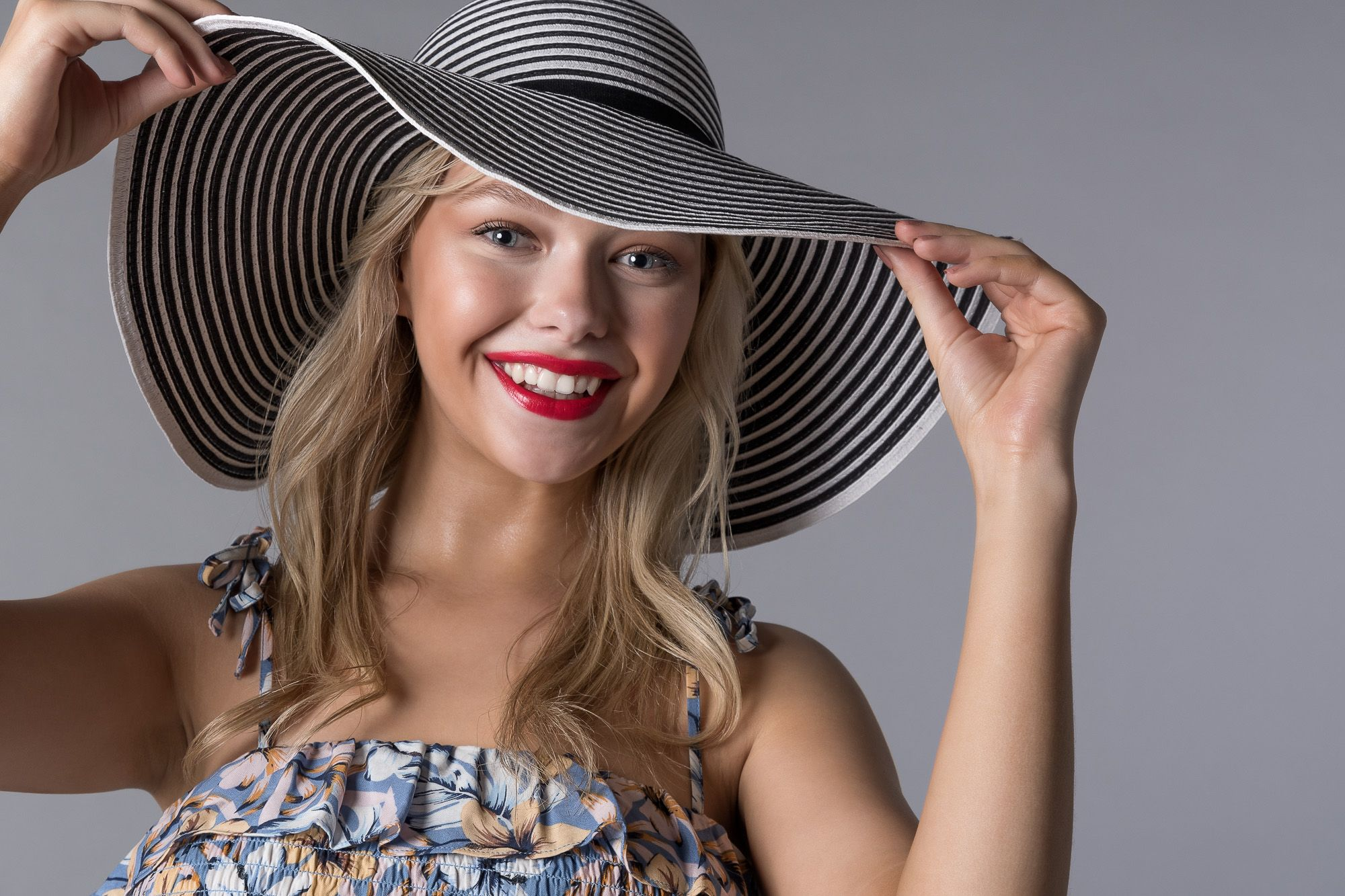 Smiling woman wear floral top and large striped hat on plain grey background